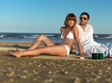 young couple relaxing by the sea