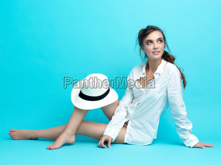 young woman white shirt hat blue