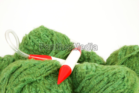 green wool with knitting needle