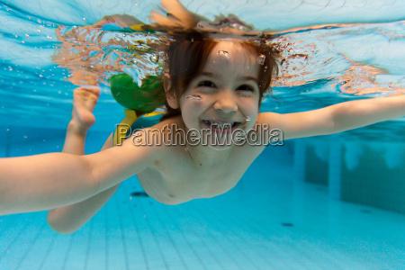 das maedchen laechelt schwimmen unter wasser