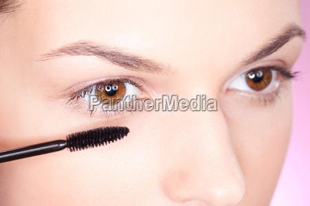 huebsche frau die mascara auf augenhoehe