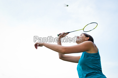 pretty young woman playing badminton in