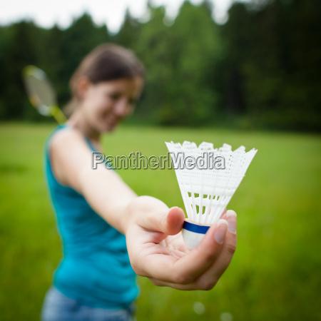 huebsche junge frau spielt badminton in