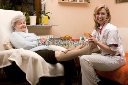 altenpflegerin verbindet bein von seniorin