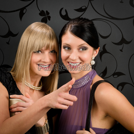 woman friends party dress point at