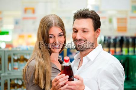 paar im supermarkt kauft getraenke