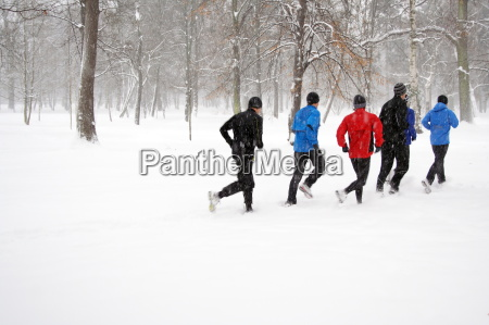 young people running in snowy park