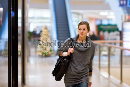 junge frau schaut beim einkaufen auf