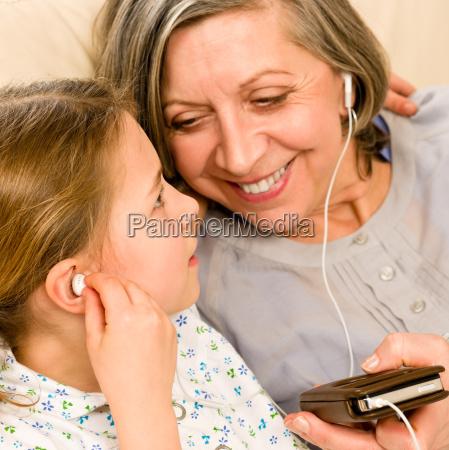 grossmutter und junges maedchen hoeren musik