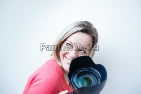 huebscher weiblicher fotograf mit ihrer digitalkamera
