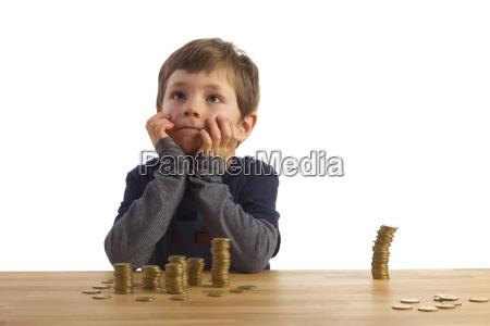 ein junge sitzt vertaeumt vor mehreren