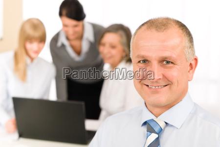 smiling geschaeftsmann waehrend der teamsitzung
