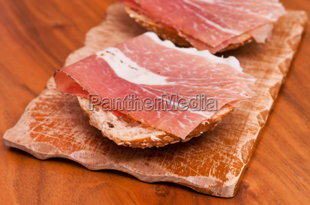 wooden board with sandwiches with smoked
