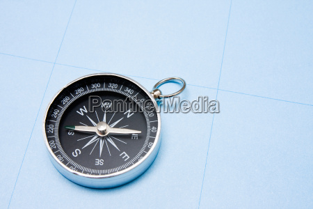 compass on blue paper background