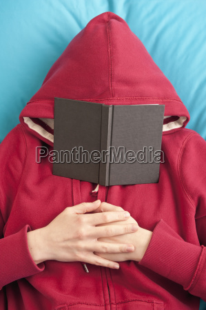 lying down with book covering face
