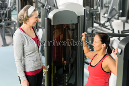 personal trainer im fitness center zeigt