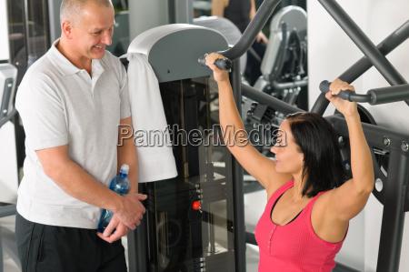 personal trainer im fitness center zeigen