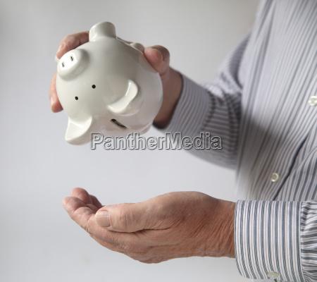 businessman emptying piggy bank