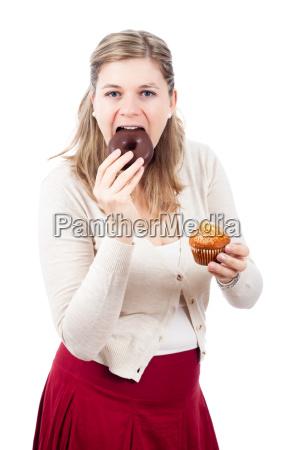 frau isst schokolade und suesse krapfen