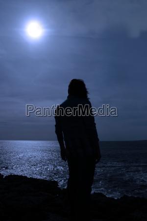 silhouette einsame frau am klippenrand