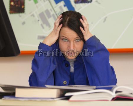 azubi im unterricht in arbeitskleidung bein