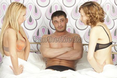 man between two women in bed