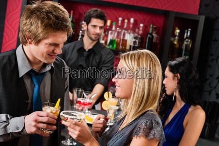 glueckliche freunde am cocktail bar getraenke