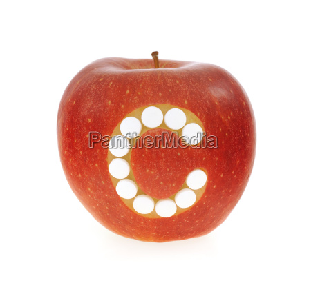 red apple with vitamin c pills