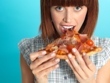 beautiful young woman eating a pizza