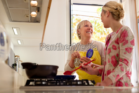 mom and daughter cooking in home