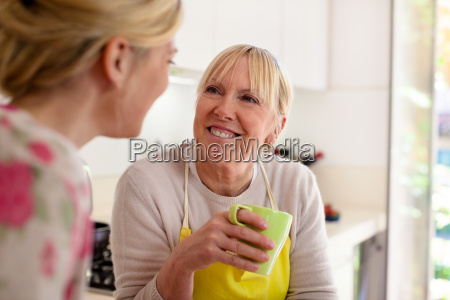 mother and daughter talking drinking coffee
