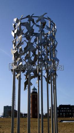 vogelflug kunstwerk mit leuchtturmcuxhaven