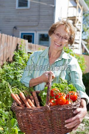 senior woman holding basket full of