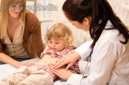 pediatrician examine child tummy at office