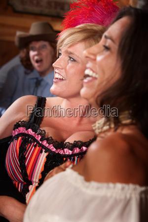 drei lachende frauen in einem salon