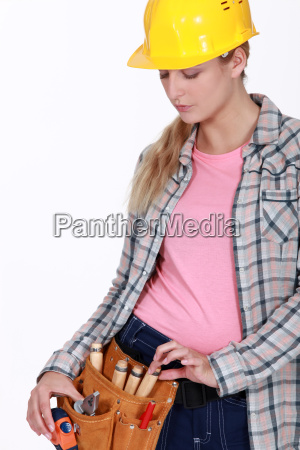 tradeswoman pulling a tool from her
