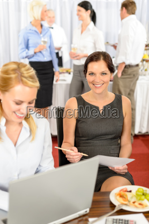 business woman work during company buffet
