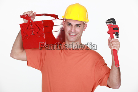 craftsman carrying toolbox over his shoulder