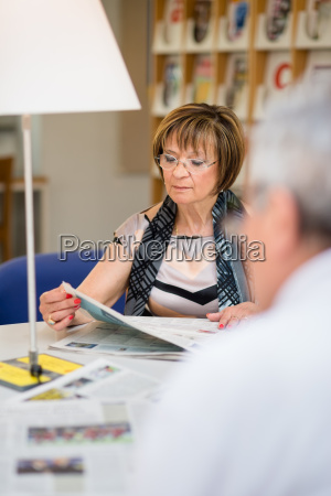 old woman reading newspaper with husband