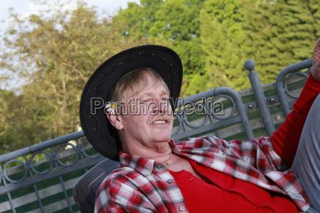 rentner entspannt auf einem balkon