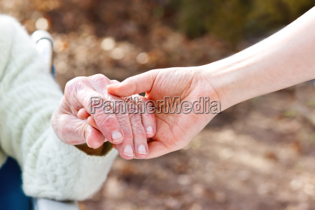 senior lady holding hands with young