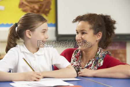 schulmaedchen studieren im klassenzimmer mit lehrer