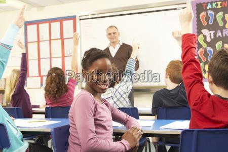schulkinder die im klassenzimmer mit lehrer