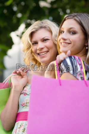 two female friends smiling with shopping