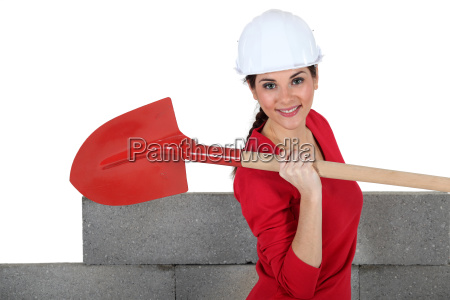 woman stood by unfinished wall with