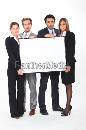 four young executives holding a framed