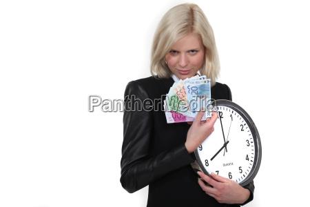 geschaeftsfrau mit uhr und bargeld