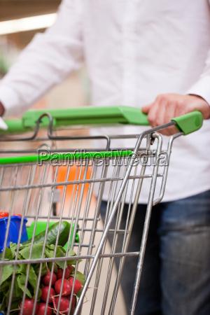 young man pushing shopping cart into
