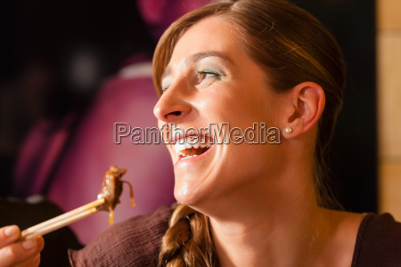 young woman eating in a thai
