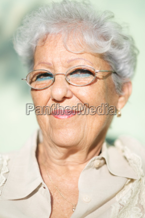 old woman with eyeglasses smiling and